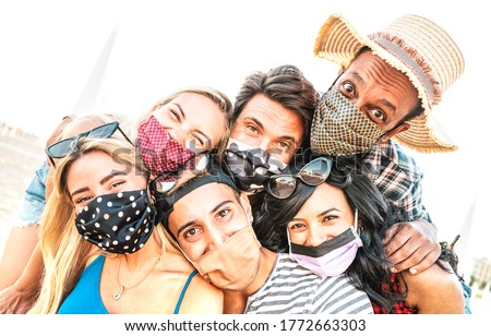 Multiracial milenial friends taking selfie smiling behind face masks - New normal summer friendship concept with young people having fun together - Warm bright backlight filter with tilted composition #1772663303