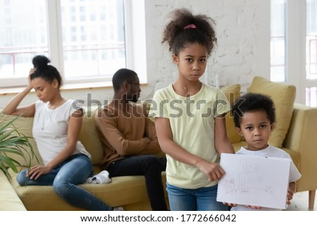 Unhappy little African siblings holding drawing where happy full family and house looks at camera. Psychological Effects of divorce on kids, parents separation break up, dysfunctional family concept