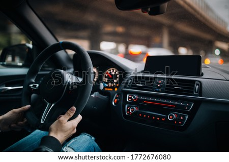 Driving a car in city. Man driving his modern sport car at the city Royalty-Free Stock Photo #1772676080