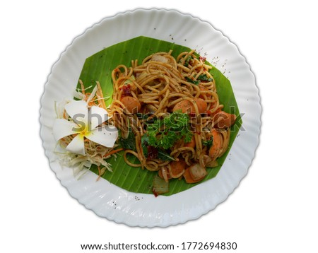Spaghetti Sausage Sausage served on a white plate with banana leaves. Isolate picture