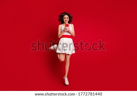 Full size photo of pretty crazy lady jumping high up good mood hold telephone hands chatting friends modern user wear white short dress shoes isolated red color background