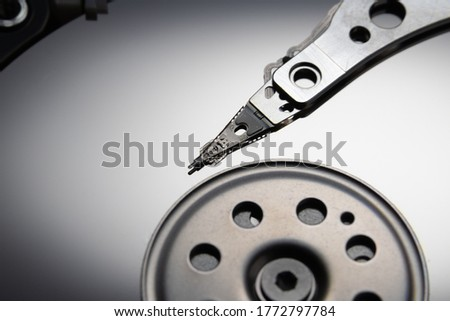 Open hard disk drive. The concept of data storage. Data array. Magnetic head on the surface of the disk.