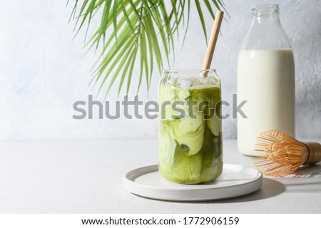 Iced Green matcha tea mixed with ice cube and milk in latte glass on white. Space for text. Close up. #1772906159