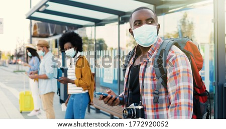 Mixed-races young males and females people im medical masks standing in line at bus stop. Keeping safe social distance. African American stylish man tourist outdoor waiting for transport. Tourists. #1772920052