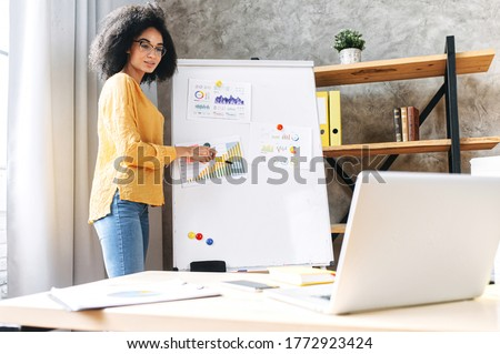 Confident young african-american woman conducts webinar, business training online. Online coach stands near flip chart in front of laptop and explains something to online audience Royalty-Free Stock Photo #1772923424