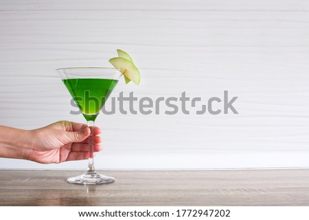 Female hand with green appletini cocktail in glass on wooden table. Copy space #1772947202