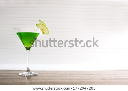Green appletini cocktail on wooden table. Copy space #1772947205