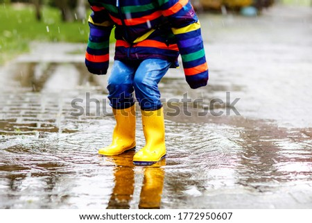 Close-up of kid wearing yellow rain boots and walking during sleet, rain and snow on cold day. Child in colorful fashion casual clothes jumping in a puddle. Having fun outdoors #1772950607