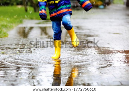 Close-up of kid wearing yellow rain boots and walking during sleet, rain and snow on cold day. Child in colorful fashion casual clothes jumping in a puddle. Having fun outdoors #1772950610