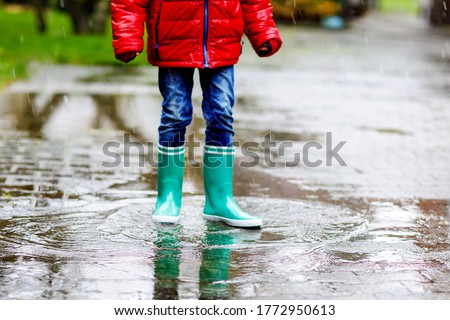 Close-up of kid wearing yellow rain boots and walking during sleet, rain and snow on cold day. Child in colorful fashion casual clothes jumping in a puddle. Having fun outdoors #1772950613