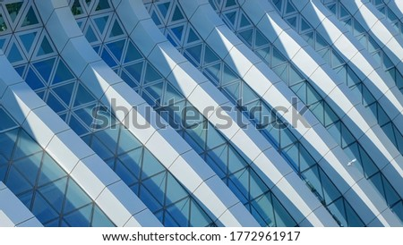 Modern architecture. Abstract pattern of shadows and light on curved diagonal lines of contemporary facade.Fragment of the facade of glass building. #1772961917