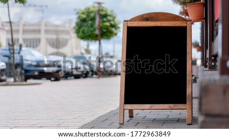 empty black chalkboard in wooden frame stands near street cafe entrance for menu information food business concept