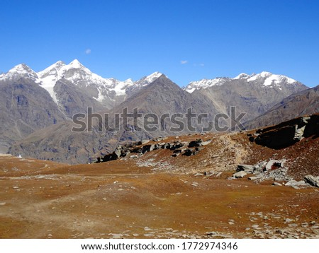 A scenic and breathtaking view of mountain peaks from rock and sand to snow all in one pic