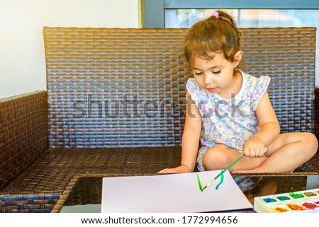 Little child drawing a picture with paint and brush. Cute small beautiful girl painting picture in garden, outdoors at home in backyard. Summer fun. Soft focus.