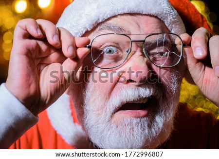 Santa holds broken eyeglasses. Christmas. Santa man with broken glasses. Surprised Santa holds broken eye glasses. Santa Claus looking through cracked eyeglasses. #1772996807