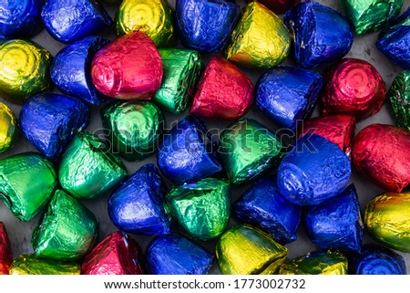 Cheap bonbons in multicolored foil wraps piled up on table. Colorful sweets background