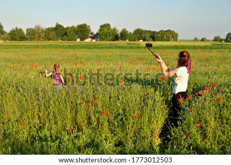 Mom takes pictures on the phone as a daughter walks in a field of poppies.
