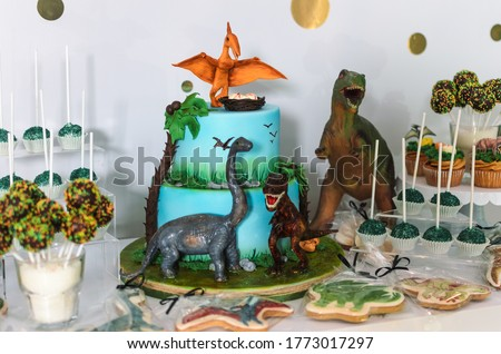 Art cake with different dinosaurs. Gift for the boy. Picture for a menu or a confectionery catalog.