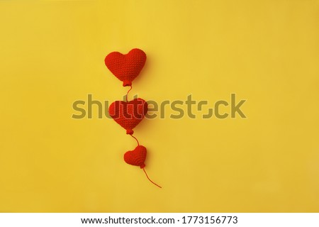 three knitted red heart-shaped balloons in row on yellow background, concept of love