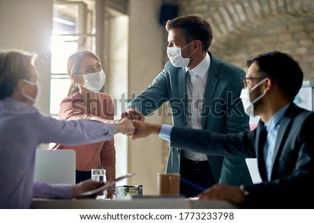 Group of colleagues wearing protective face masks and fist bumping while having business meeting during coronavirus pandemic.  Royalty-Free Stock Photo #1773233798