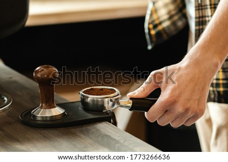 Barista presses ground coffee using tamper. Professional barista working makeing coffee with coffee machine. Hot pouring drink concept. Toned picture