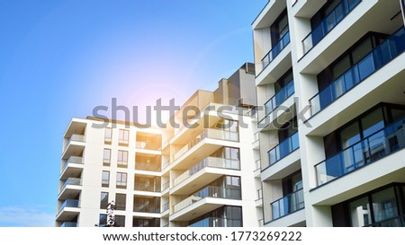Modern apartment buildings on a sunny day with a blue sky. Facade of a modern apartment building. Glass surface with sunlight.