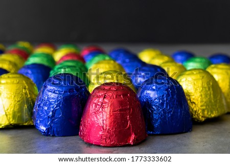 Cheap chocolate bonbons in multicolored wrapping foil on dark background. Focus on foreground with gradual blur into the background. Colorful sweets close-up with empty space for text on top