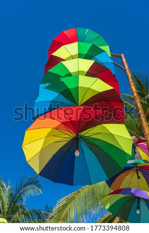 Street lamps decorated with colorful umbrellas hang on a pillar in street against the blue sky and green coconut palm tree on a sunny day, Vietnam #1773394808