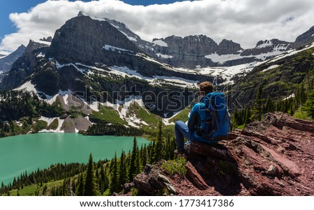 Hiker in glacier national park enjoying the view of Grinnell lake Royalty-Free Stock Photo #1773417386
