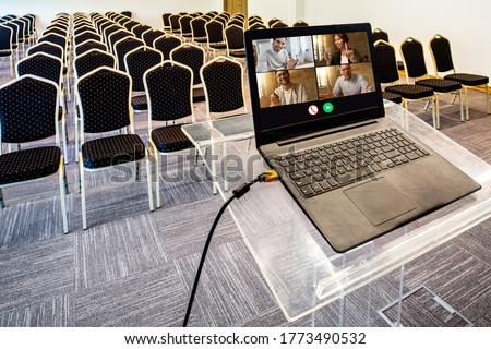 Group of happy business coworkers having video call over laptop in empty conference hall.  Royalty-Free Stock Photo #1773490532