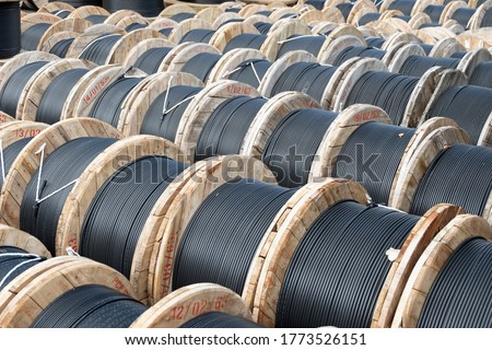 Wooden Coils Of Electric Cable Outdoor. High and low voltage cables in the storage. Royalty-Free Stock Photo #1773526151