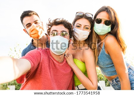 Group of friends taking a selfie at park wearing medical masks to protect - Conceptual Coronavirus virus quarantine - Copy space - Multiracial people having fun together