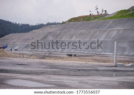 A view of soil nailing retaining wall for slope protection at construction site during the earthwork phase. Royalty-Free Stock Photo #1773556037