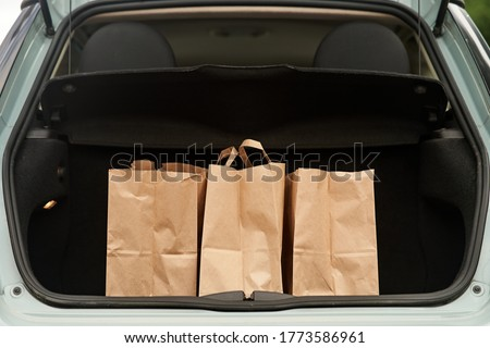 Blank paper bags in a car trunk Royalty-Free Stock Photo #1773586961