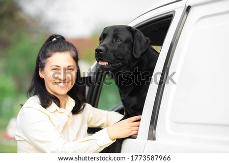 Woman with her black Labrador dog in the car #1773587966