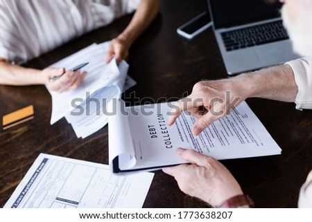 Cropped view of senior man pointing at paper with debt collection lettering near gadgets and wife at home Royalty-Free Stock Photo #1773638207