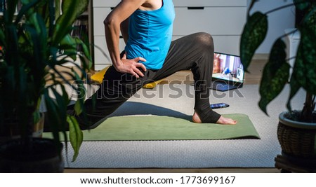 woman doing yoga at home surrounded by plants