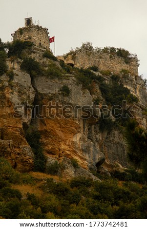 Image of the iconic Castle of Gozne on top of steep cliffs. The castle is located on top of Taurus mountains in Mersin Province of Turkey. A Turkish flag and a picture of Ataturk is seen on the walls.
