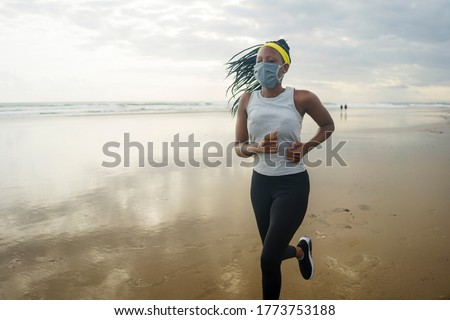 young attractive black girl post quarantine jogging - new normal running workout of athletic and fit African American woman at beautiful beach wearing face mask #1773753188