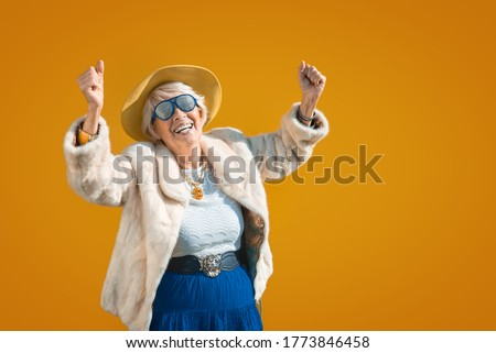 Happy and playful senior woman having fun - Portrait of a beautiful lady above 70 years old with stylish clothes, concepts about senior people Royalty-Free Stock Photo #1773846458