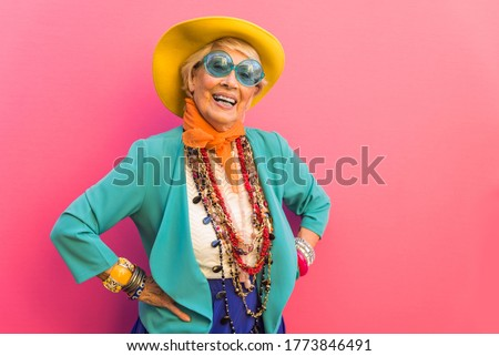 Happy and playful senior woman having fun - Portrait of a beautiful lady above 70 years old with stylish clothes, concepts about senior people Royalty-Free Stock Photo #1773846491
