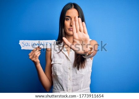 Young beautiful brunette woman holding paper with solidarity message over blue background with open hand doing stop sign with serious and confident expression, defense gesture