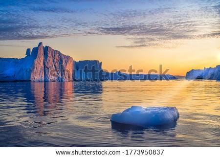 Greenland Ilulissat glaciers at ocean at polar night with sun rays #1773950837