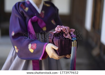 Woman in Korean traditional clothes holding traditional package Royalty-Free Stock Photo #1773979652