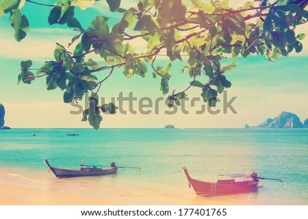 Vintage stylized photo of traditional longtail boats at Andaman sea, Thailand