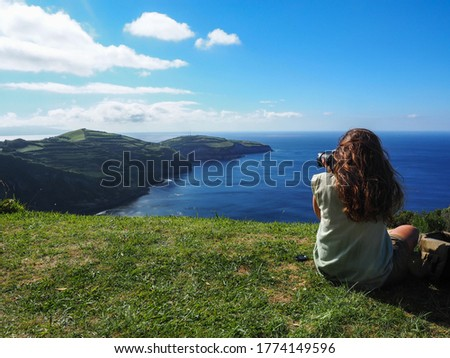 Young girl sitting and taking pictures on a cliff off the coast of San Miguel Island