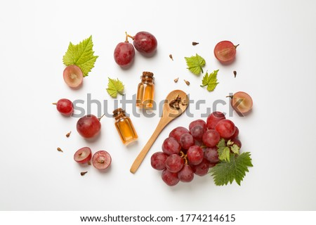 Composition with bottles of natural grape seed oil on white background, top view. Organic cosmetic Royalty-Free Stock Photo #1774214615