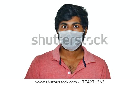 Young Indian man wearing wearing single layer mask and looking fearfully.  isolated on white background