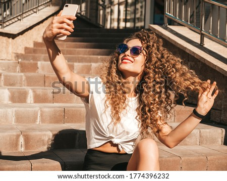 Beautiful smiling model with afro curls hairstyle dressed in summer hipster clothes.Sexy carefree girl sitting on  stairs in the street in sunglasses.Taking selfie self portrait photos on smartphone