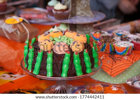 Halloween chocolate cake with green fingers and pumpking faces displayed with other foods.  #1774442411